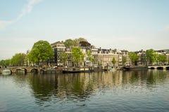 Σπίτια καναλιών του Άμστερνταμ μια ηλιόλουστη ημέρα Στοκ Εικόνες