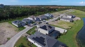 Σπίτια με τις επιτροπές ηλιακής ενέργειας στις στέγες, μικρό suburbian χωριό eco, 4k φιλμ μικρού μήκους