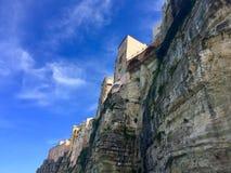 Σπίτια που στηρίζονται στους καθαρούς απότομους βράχους της πόλης Tropea στην Ιταλία Στοκ Φωτογραφία