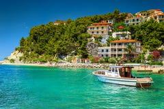 Σπίτια πολυτέλειας με τη βάρκα τουριστών στο λιμάνι, Brela, Δαλματία, Κροατία στοκ εικόνα με δικαίωμα ελεύθερης χρήσης