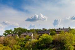 Σπίτια στην πράσινη κλίση και το φωτεινό ουρανό στοκ εικόνα με δικαίωμα ελεύθερης χρήσης