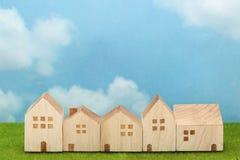 Σπίτια στην πράσινη χλόη πέρα από το μπλε ουρανό και τα σύννεφα Στοκ Εικόνες