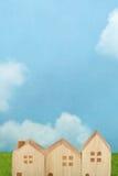 Σπίτια στην πράσινη χλόη πέρα από το μπλε ουρανό και τα σύννεφα Στοκ Εικόνα