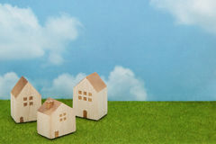 Σπίτια στην πράσινη χλόη πέρα από το μπλε ουρανό και τα σύννεφα Στοκ φωτογραφία με δικαίωμα ελεύθερης χρήσης
