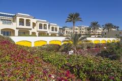 Σπίτια στο μεγάλο θέρετρο οάσεων ξενοδοχείων ενάντια στα ανθίζοντας φυτά Στοκ Φωτογραφίες