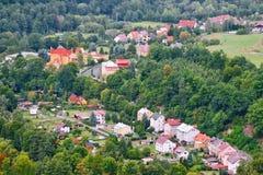 Σπίτια στο χωριό Kyselka μεταξύ των δέντρων που αντιμετωπίζονται από την επιφυλακή πετρών πάνω από το λόφο Bucina στο τσεχικό φθι Στοκ Εικόνες