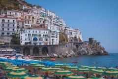 Σπίτια Cliffside και ομπρέλες παραλιών στην πόλη της Αμάλφης, Ιταλία στοκ φωτογραφία