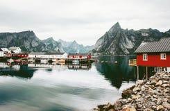 Σπίτια rorbu της Νορβηγίας και βράχοι βουνών πέρα από το φιορδ Στοκ Εικόνες