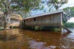 Σπίτια Woode που στηρίζονται στα υψηλά ξυλοπόδαρα πέρα από το νερό, τροπικό δάσος του Αμαζονίου Στοκ Εικόνες