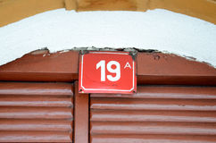 Σπίτι αριθμός 19 σε ένα κόκκινο πιάτο Στοκ Φωτογραφίες