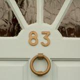 Σπίτι αριθμός 83 σημάδι στην πόρτα με τα ρόπτρα πορτών ορείχαλκου Στοκ φωτογραφίες με δικαίωμα ελεύθερης χρήσης