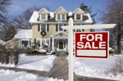 Σπίτι για το σημάδι πώλησης μπροστά από το χιονώδες καινούργιο σπίτι Στοκ Εικόνες