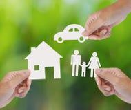 Σπίτι εγγράφου εκμετάλλευσης χεριών, αυτοκίνητο, οικογένεια στο πράσινο υπόβαθρο Στοκ Φωτογραφίες