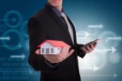 Σπίτι εκμετάλλευσης χεριών επιχειρηματιών που αντιπροσωπεύει την εγχώρια ιδιοκτησία και το τ στοκ φωτογραφία