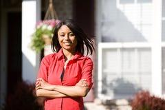 Σπίτι: Εύθυμη γυναίκα έξω από το σπίτι Στοκ Φωτογραφίες