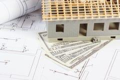 Σπίτι κάτω από την κατασκευή και το δολάριο νομισμάτων στα ηλεκτρικά σχέδια και διαγράμματα για το πρόγραμμα, έννοια εγχώριων δαπ Στοκ Φωτογραφία