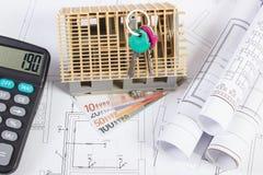 Σπίτι κάτω από την κατασκευή, κλειδιά, υπολογιστής, ευρο- και ηλεκτρικά σχέδια νομισμάτων, έννοια της οικοδόμησης του σπιτιού Στοκ Εικόνα