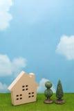 Σπίτι και δέντρα στην πράσινη χλόη πέρα από το μπλε ουρανό και τα σύννεφα Στοκ φωτογραφία με δικαίωμα ελεύθερης χρήσης