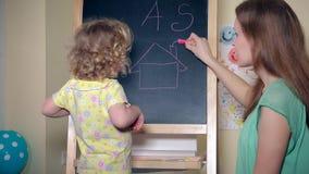 Σπίτι και επιστολές ζωγραφικής γυναικών για το κορίτσι παιδιών στον πίνακα με την κιμωλία απόθεμα βίντεο
