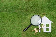 Σπίτι και κλειδί εγγράφου με την ενίσχυση - γυαλί, πράσινο κυνήγι διαβίωσης Στοκ Εικόνα