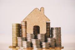 Σπίτι και σωρός νομισμάτων για την αποταμίευση για να αγοράσει ένα σπίτι στοκ εικόνα με δικαίωμα ελεύθερης χρήσης