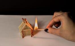 Σπίτι και χέρι αντιστοιχιών με το κάψιμο της πυρκαγιάς - κίνδυνος ατυχήματος Στοκ φωτογραφία με δικαίωμα ελεύθερης χρήσης
