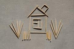 Σπίτι και χλόη φιαγμένα από οδοντογλυφίδες στο σκυρόδεμα Στοκ Φωτογραφίες