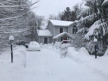 Σπίτι κατά τη διάρκεια των αυτοκινήτων μιας χιονιού θύελλας driveway στοκ εικόνες