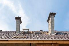 σπίτι κατασκευής κάτω Εγκατάσταση κεραμιδιών υλικού κατασκευής σκεπής Νέα στέγη με το φεγγίτη και τις καπνοδόχους Στοκ Εικόνα