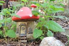 Σπίτι μανιταριών κήπων φαντασίας νεράιδων ή στοιχειών μεταξύ των εγκαταστάσεων officinalis της Melissa λεμόνι-βάλσαμου στοκ εικόνες