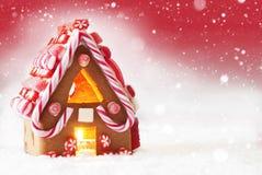 Σπίτι μελοψωμάτων, κόκκινο υπόβαθρο με Snowflakes, διάστημα αντιγράφων Στοκ Εικόνες