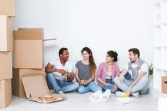 σπίτι νέο Φίλοι που κάθονται στο πάτωμα στο νέο διαμέρισμα και που χαλαρώνουν μετά από να καθαρίσει και να ανοίξει Στοκ Εικόνες