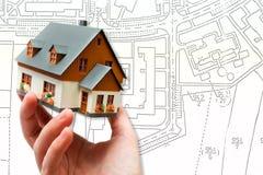 Σπίτι νέων μοντέλων εκμετάλλευσης χεριών και σχέδιο σχεδιαγραμμάτων αρχιτεκτονικής στοκ εικόνα με δικαίωμα ελεύθερης χρήσης