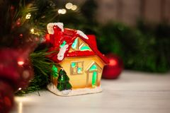 Σπίτι παιχνιδιών Χριστουγέννων με μια κόκκινη στέγη και παράθυρα με το πράσινο φως στοκ εικόνες