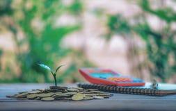 Σπίτι που τοποθετείται στα νομίσματα Το σημειωματάριο και η μάνδρα προετοιμάζουν τα χρήματα αποταμίευσης προγραμματισμού των νομι στοκ εικόνες