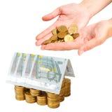 Σπίτι που χτίζεται των νομισμάτων και των τραπεζογραμματίων που απομονώνονται Στοκ εικόνα με δικαίωμα ελεύθερης χρήσης