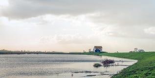 Σπίτι σε ένα ανάχωμα σε ένα πλημμυρισμένο πόλντερ Στοκ Φωτογραφίες