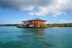 Σπίτι στα ξυλοπόδαρα πέρα από το νερό της καραϊβικής θάλασσας Στοκ Εικόνα