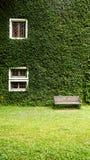 Σπίτι στην επαρχία με τον τοίχο εγκαταστάσεων Coatbuttons μεταξύ του πράσινου natu Στοκ φωτογραφία με δικαίωμα ελεύθερης χρήσης