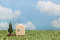 Σπίτι στην πράσινη χλόη πέρα από το μπλε ουρανό και τα σύννεφα Στοκ φωτογραφία με δικαίωμα ελεύθερης χρήσης