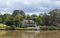 Σπίτι στον ποταμό στο Queensland Αυστραλία με τους φοίνικες και τα ψηλά δέντρα gumn κάτω από έναν θυελλώδη ουρανό την άνοιξη Στοκ φωτογραφία με δικαίωμα ελεύθερης χρήσης