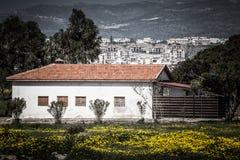 Σπίτι στο λιβάδι που αγνοεί την πόλη βαμμένος στοκ εικόνα