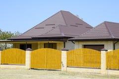 Σπίτι τούβλου με τη ζαρωμένη στέγη σχεδιαγράμματος μετάλλων και τον ξύλινο φράκτη Στοκ εικόνα με δικαίωμα ελεύθερης χρήσης