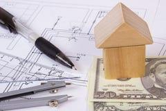 Σπίτι των ξύλινων φραγμών, του δολαρίου νομισμάτων και των εξαρτημάτων για το σχέδιο, έννοια σπιτιών κτηρίου Στοκ φωτογραφία με δικαίωμα ελεύθερης χρήσης