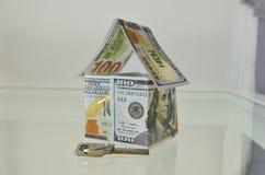 Σπίτι φιαγμένο από λογαριασμούς 100 δολαρίων και ένα κλειδί στο μέτωπο Στοκ εικόνα με δικαίωμα ελεύθερης χρήσης