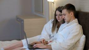 Σπίτι lap-top ξεφυλλίσματος γυναικών ανδρών ελεύθερου χρόνου ζεύγους απόθεμα βίντεο