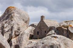 Σπίτι Meneham που περιβάλλεται από τους μεγάλους βράχους Βρετάνη, Γαλλία Στοκ Φωτογραφίες
