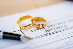 Σπασμένα γαμήλια δαχτυλίδια στο διάταγμα διαζυγίου στοκ εικόνες