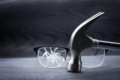 σπασμένα γυαλιά με μια σφύρα μετάλλων στο μαύρο υπόβαθρο Στοκ Εικόνες