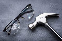 σπασμένα γυαλιά με μια σφύρα μετάλλων στο μαύρο υπόβαθρο Στοκ φωτογραφία με δικαίωμα ελεύθερης χρήσης